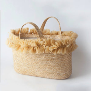 The Linea Light Cesto Medium basket is made of natural straw and embellished with a garland of natural raffia by Patrizia Fabri Hats in Rome, Italy